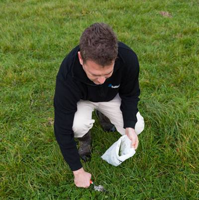 a man testing soil for fertiliser